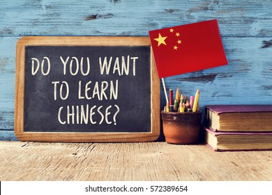 a chalkboard with the question do you want to learn chinese?, a pot with pencils, some old books and the flag of china on a rustic wooden surface