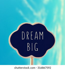 a chalkboard in the shape of a thought bubble with the text dream big, against the blue sky