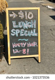 A chalkboard sign with handwritten lunch special and happy hour offers stands on the sidewalk in front of a restaurant in Harlem, New York.
