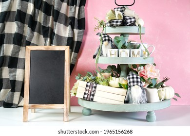 Chalkboard sign with on-trend farmhouse aesthetic three tiered tray decor filled with white pumpkins, cute black plaid gnomes, and farmhouse style stack of books mockup. Modern blush pink background. - Shutterstock ID 1965156268