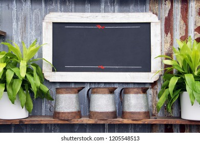 Chalkboard sign with plants on a weathered background. Add your own message, menu or text.