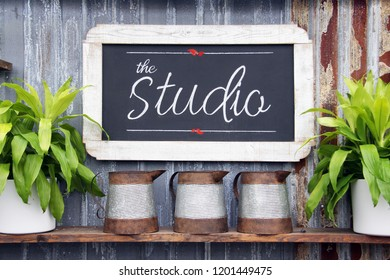 Chalkboard studio sign with plants on a weathered background.