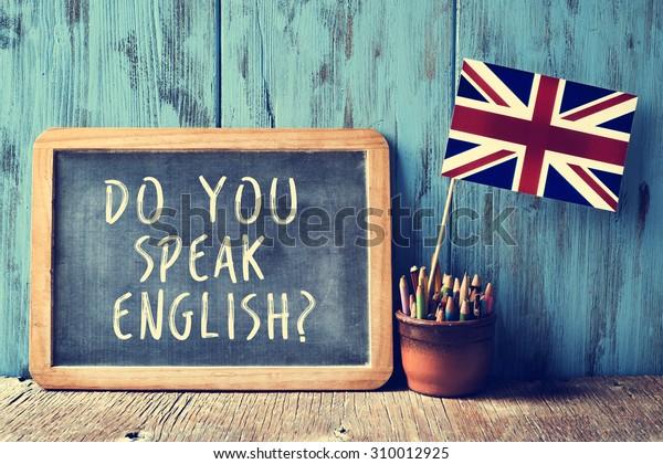 ¿Un pizarrón con el texto habla inglés? escrito en él, una olla con lápices y la bandera del Reino Unido, en un escritorio de madera, con efecto filtro