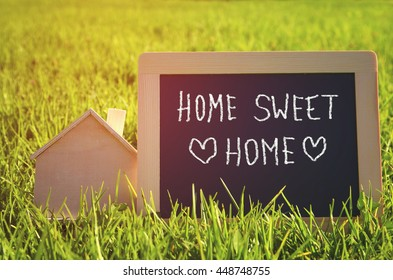 chalkboard with the text home sweet home next to wooden small house in the grass