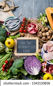 a chalkboard with the text say no to processed food on a pile of unprocessed food, such as different raw fruits and vegetables, some legumes and nuts, some pieces of chicken and some fishes