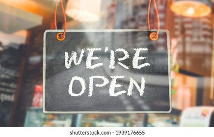 chalkboard of We're Open hang on door or window of business shop