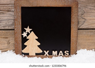 Chalkboard with wooden decoration in front of a wood background