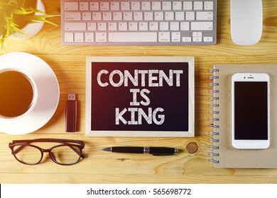 Chalkboard written CONTENT IS KING on wooden desk with flare effect