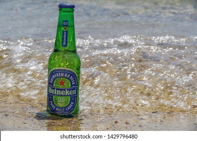 Chalkidiki, Greece - June 15 2019: Heineken zero alcohol beer bottle on sand by the sea. Sunny view of non-alcoholic lager beer on a 33cl glass bottle partly submerged on a sandy beach with low waves.