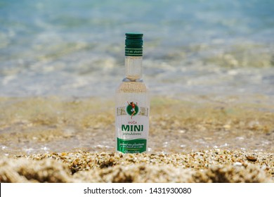 Chalkidiki, Greece - June 22 2019: Greek ouzo Mini brand bottle on sand by the sea. Sunny view of a 200 ml glass bottle of traditional alcoholic ouzo drink with anise, partly submerged on sandy beach.