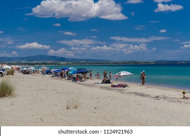 Chalkidiki, Greece - June 30 2018: Greek Mediterranean beach with crowd. Bathers resting on beach chairs under sun umbrellas at a sandy leisure beach in Chalkidiki peninsula.