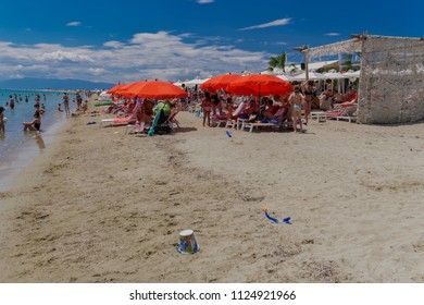 Chalkidiki, Greece - June 30 2018: Greek Mediterranean beach bar with crowd. Bathers resting on beach chairs under red and white sun umbrellas at a sandy leisure beach in Chalkidiki peninsula.