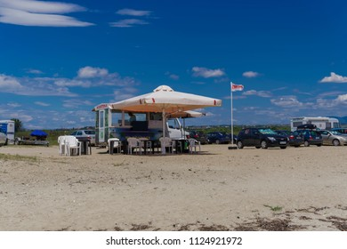 Chalkidiki, Greece - June 30 2018: Canteen fast food truck at a Greek beach. Street food vehicle, called kantina, with plastic tables and chairs, parked at a sandy beach in Chalkidiki peninsula.