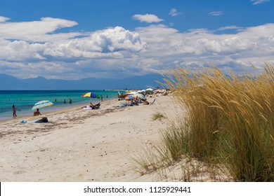 Chalkidiki, Greece - June 30 2018: Greek Mediterranean beach with crowd. Bathers with sun umbrellas at a sandy beach under blue sky with clouds in Chalkidiki peninsula, Greece.