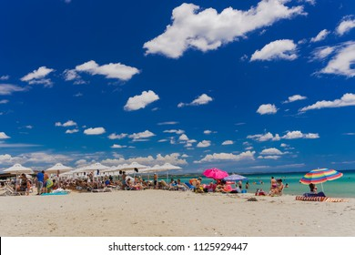 Chalkidiki, Greece - June 30 2018: Greek Mediterranean beach bar with crowd. Bathers at beach chairs under sun umbrellas at a sandy beach in Chalkidiki peninsula, Greece.