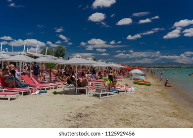 Chalkidiki, Greece - June 30 2018: Greek Mediterranean beach bar with crowd. Bathers with sun umbrellas at a sandy beach under blue sky with clouds in Chalkidiki peninsula, Greece.
