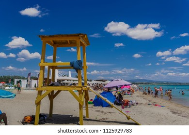 Chalkidiki, Greece - June 30 2018: Mediterranean beach lifeguard wooden tower. Bathers under blue sky at beach bar at a sandy beach in Chalkidiki peninsula, Greece.