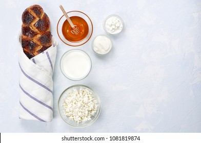 Challah bread with poppy seeds, honey and set of dairy products comprising cottage cheese, sour cream and milk on a blue background. Jewish holiday Shavuot concept. Copy space, top view, flat lay