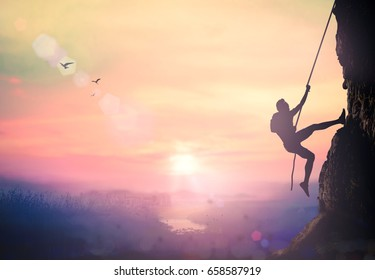 Challenge concept: Silhouette bold heroic man try to climb with rope over natural rocky wall wide valley autumn sunset mountain background