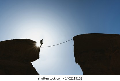 Challenge, risk, concentration and bravery concept. Silhouette a man balance walking on rope over precipice