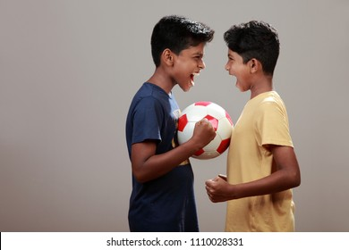 Challenging young boys with a soccer ball in between them