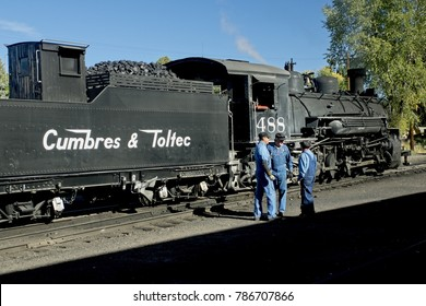 Chama NM, USA, Sept. 19, 2017: Railroad workers chat as a vintage steam locomoitve from the Cumbres & Toltec warms up in the railyard before an autumn excursion.