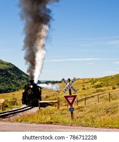 Chama NM, USA, Sept. 19, 2017: A vintage steam locomoitve from the Cumbres & Toltec railroad approaches a railroad crossing as it climbs toward Chama Pass in early autumn.