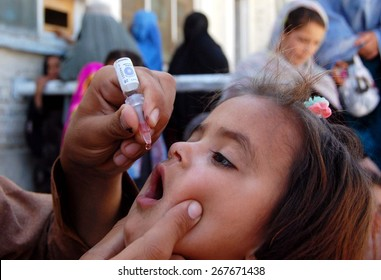 CHAMAN, PAKISTAN - APR 08: Health worker administrates polio-vaccine drops to a child during anti-polio immunization campaign at Pak-Afghan Border on April 08, 2015 in Chaman.
