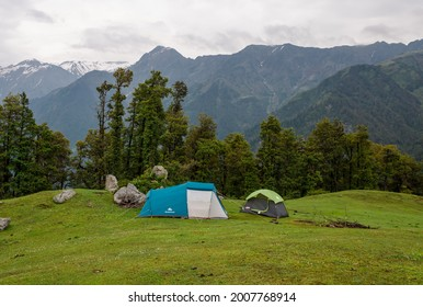 CHAMBA, INDIA - Jun 20, 2021: Two tents on mountains covered in greenery under a cloudy sky in Chamba, India
