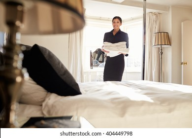Chambermaid carrying linen in hotel bedroom, low angle view