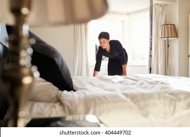 Chambermaid changing bed linen on the bed in a hotel room