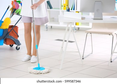 Chambermaid cleaning floor in office