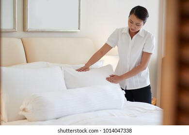 Chambermaid putting pillows on bed in hotel room