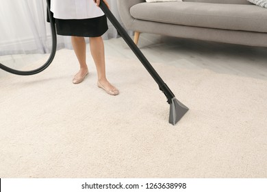 Chambermaid removing dirt from carpet with vacuum cleaner indoors, closeup. Space for text