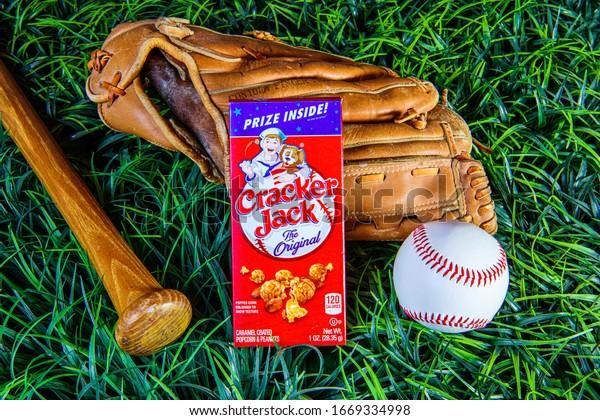 Chambersburg Pennsylvania USA 3/7/2020 vintage cracker jack box on old baseball glove on green grass with baseball and bat