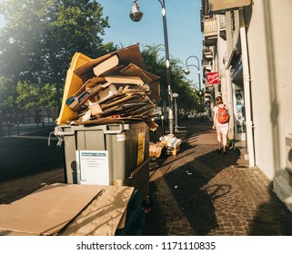 Chambery, France - Aug16, 2018: French street in Chambery with dumpsters being full with paper cardboard boxes garbage woman walking nearby