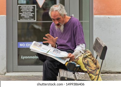 Chambery Savoy, France - August 2 2019: Man reading funny news  in the local newspaper