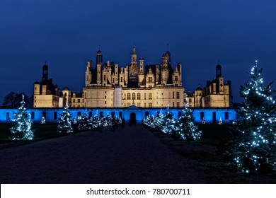 Chambord, France - December 24, 2017: Chambord castle with christmas trees at night. Christmas eve