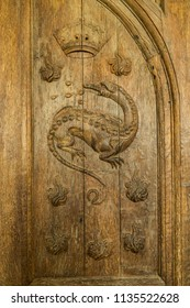 CHAMBORD, FRANCE - June 14, 2018: Carved figure of a salamander in an old wooden door in Chateau de Chambord in France. The salamander, believed to resist flames, was the emblem of Francis I.