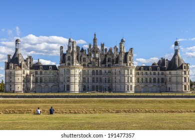 CHAMBORD,FRANCE-SEPT 08:Unidentified couple siting on the grass and admiring the Chambord Castle on September 08,2013. Chambord is royal medieval French castle in Loire Valley - UNESCO heritage site.