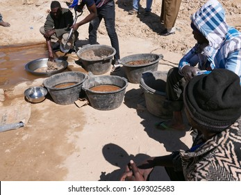 Chami, Mauritania - January 20, 2019: artisanal miner using water to separate gold from crushed ore mixed with mercury.
