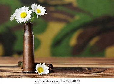 Chamomile in bullet case.On wooden table on military background.Concept photography no war.Make love no war.Copy space