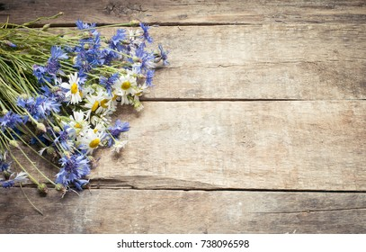 Chamomile and cornflowers on a wooden background/toned photo