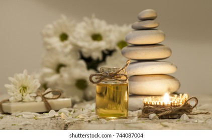 Chamomile essential oil, bouquet of chamomile flowers, stack of white rocks and candle