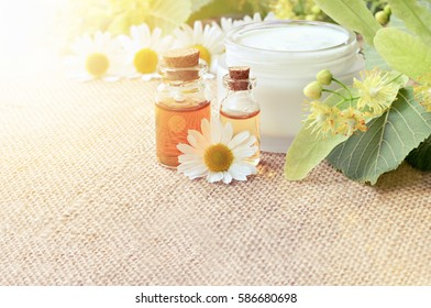 Chamomile extract organic cosmetics for beauty care. Bottle of essential oils, fresh holistic blossom, sunflare summery effect, soft focus