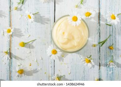 Kamillenblumen und Babycreme auf weißem Holztisch direkt darüber