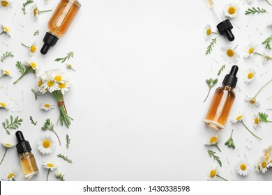 Chamomile flowers and cosmetic bottles of essential oil on white background, top view. Space for text