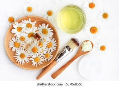 Chamomile flowers and extracted cosmetic beauty products top view. Essential oil, tonic, facial mask, brush and spoon. Botanical skincare preparation. Herbal spa treatment