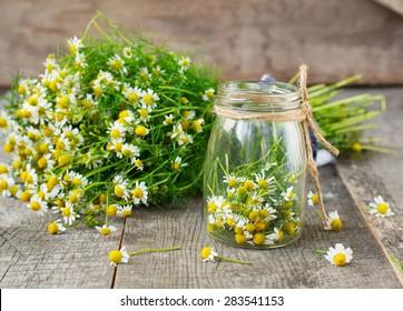 fleurs de camomille sur fond bois dans un bocal en verre