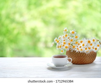 chamomile flowers and tea cup on white table. Summer romantic  Breakfast in garden. rustic composition. copy space.